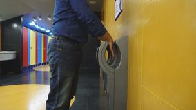 Man dry hands on modern hand dryer in toilet. 4k stock video