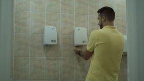The man is drying his hands in the toilet. The man dries his hands in the toilet and using a hand dryer stock video footage