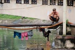 Man drying washing in Hanoi. Man squats above river as he dries washing in Hanoi, Vietnam Stock Photography