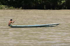 Man in a dugout canoe on the Napo river in Ecuador. June 6, 2017 Misahualli, Ecuador:  canoes are used as transportation on river Napo in the Amazon area of the Royalty Free Stock Photography