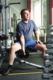 Man with dumb-bell. Man in shirt and shorts at gym with dumb-bell looking sideways Royalty Free Stock Photo