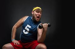 Man with a dumbbell. Fat man do exercise with a dumbbell over grey Royalty Free Stock Images
