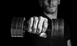 Man with dumbbell, focus on dumbbell. Muscular man holds dumbbell, focus on dumbbell, monochrome image royalty free stock photo