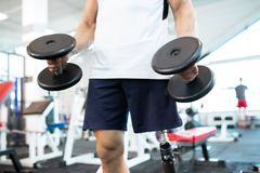 Man with dumbbells. Close-up of disabled man standing with dumbbells royalty free stock images
