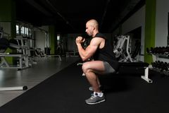 Man With Dumbbells Exercising Quadriceps And Glutes. Strong Man In The Gym Exercising Quadriceps And Glutes With Dumbbells - Muscular Athletic Bodybuilder Stock Image