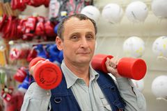 Man with dumbbells in sport store. Man with dumbbells in a sport store Stock Photos