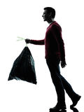 Man dumping garbage bag. In silhouettes on white background royalty free stock photo