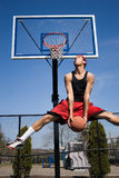 Man Dunking a Basketball. A young basketball player driving to the hoop Royalty Free Stock Photo
