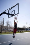 Man Dunking a Basketball. A young basketball player driving to the hoop Royalty Free Stock Photography