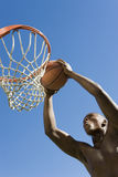 Man Dunking Basketball Into Hoop Against Blue Sky. Low angle view of determined young man dunking basketball into hoop against clear blue sky Stock Images