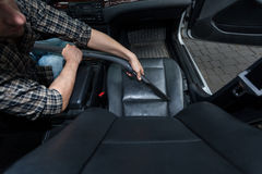 Man dusting car's chair Royalty Free Stock Image