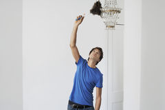 Man Dusting Crystal Chandelier In Home. Young man dusting crystal chandelier with duster in living room royalty free stock photography