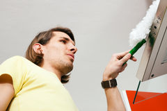 Man dusting his apartment Stock Photos
