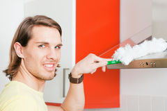 Man dusting his apartment Stock Photography
