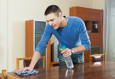 Man dusting wooden table with rag and cleanser at home Stock Photo