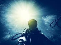 Man dykning i havet med solstrålar Royaltyfria Bilder