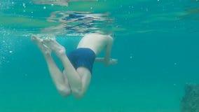 Man dykning under vatten i havet i maskering lager videofilmer