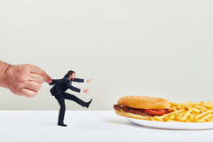 Man eagering for a junk food. Small man running to junk food but the big hand holding him over light grey background Stock Photo
