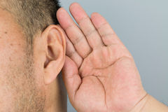 Man ear. Man holds his hand near his ear and listening stock images