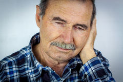 Man with ear pain. Senior man covering his ear with hand stock images