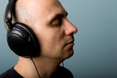 Man with ear-phones. Intimate portrait of Man with ear-phones with blue background Stock Photos