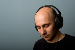 Man with ear-phones. Intimate portrait of Man with ear-phones with blue background Royalty Free Stock Photo