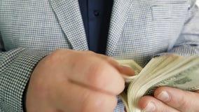 Man in a jacket counts money earnings. Man earnings in a jacket counts money stock footage