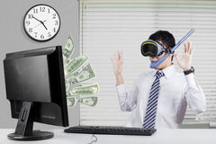 Man earns money with computer. Businessman wearing goggles and snorkel, looking at the dollar money on the monitor Royalty Free Stock Image