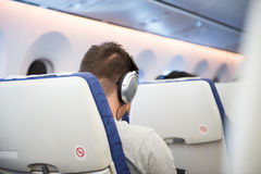 Man with earphone sit inside airplane while travel abroad. royalty free stock image