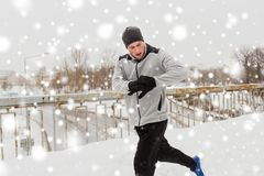 Man with earphones running along winter bridge. Fitness, sport, people, technology and healthy lifestyle concept - young man in earphones running along snow Stock Photos