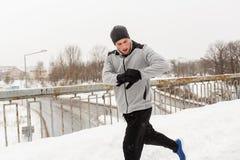 Man with earphones running along winter bridge Stock Images