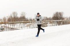 Man with earphones running along winter bridge Stock Photo