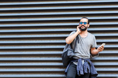 Man with earphones and smartphone on city street Royalty Free Stock Photography