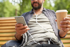 Man with earphones and smartphone drinking coffee Stock Image