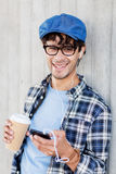 Man with earphones and smartphone drinking coffee. People, technology, leisure and lifestyle - man with earphones and smartphone drinking coffee and listening to Royalty Free Stock Photography