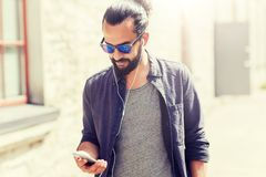 Man with earphones and smartphone walking in city. People, music, technology, leisure and lifestyle - man with earphones and smartphone walking in city Royalty Free Stock Photos