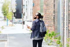 Man with earphones and smartphone walking in city Stock Photography