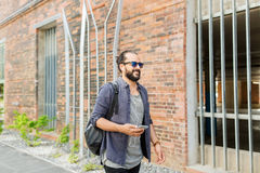 Man with earphones and smartphone walking in city Royalty Free Stock Images