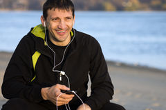Man with earphones. Smiling man with earphones is sitting outdoors along the riverside Royalty Free Stock Images