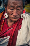 Man with earrings in Bihar. Bohdgaya, Bihar - circa January 2012: Man with tanned wrinkled face and big earrings looks down during teachings in Bohdgaya, Bihar Stock Photo
