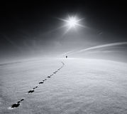 Man.Earth.Universe.Lonely man walking on snow crust field on the trail of a hare on the background of the sun and the flying plane. Abstract photo silhouette of stock images
