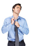 Man easing his tie against white background Stock Images