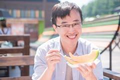 Man eat cantaloupe stock images