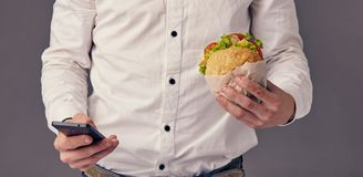 Man eat hamburger in cafe while watch video on his phone. Businessman eat hamburger in cafe while watch video on his phone Stock Image