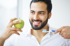 Man Eating Apple. Beautiful Girl With White Teeth Biting Apple. High Resolution Image royalty free stock photography