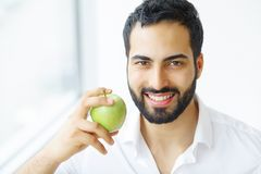 Man Eating Apple. Beautiful Girl With White Teeth Biting Apple. High Resolution Image royalty free stock image