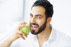 Man Eating Apple. Beautiful Girl With White Teeth Biting Apple. High Resolution Image stock photos