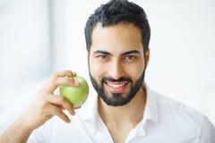 Man Eating Apple. Beautiful Girl With White Teeth Biting Apple. High Resolution Image stock photo
