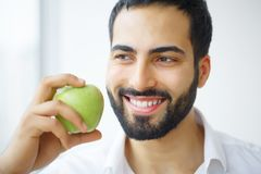 Man Eating Apple. Beautiful Girl With White Teeth Biting Apple. High Resolution Image royalty free stock images