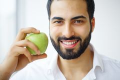 Man Eating Apple. Beautiful Girl With White Teeth Biting Apple. High Resolution Image stock photography